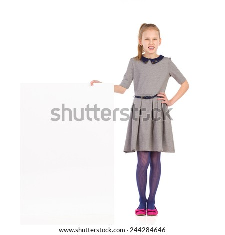 Girl in gray dress standing close to placard. Full length length studio shot isolated on white. - stock photo