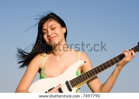 Girl in green dress playing a guitar - stock photo