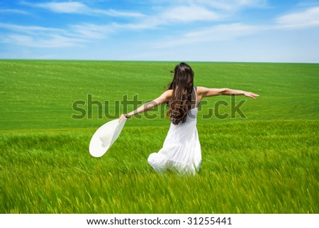 girl in green field with open arms dancing and enjoying nature - stock photo