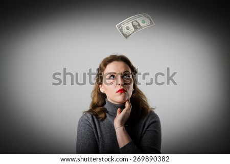 Girl in grey and falling dollar banknote. Currency and lottery concept. - stock photo