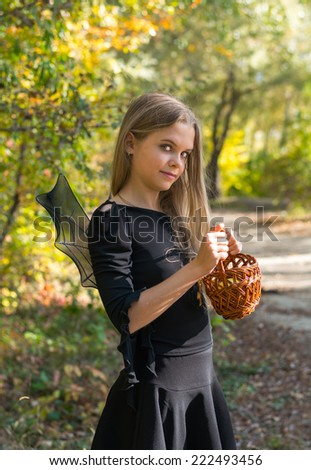 Girl in Halloween style. Girl in black with a basket, worm on the background of autumn forest, bokeh. - stock photo