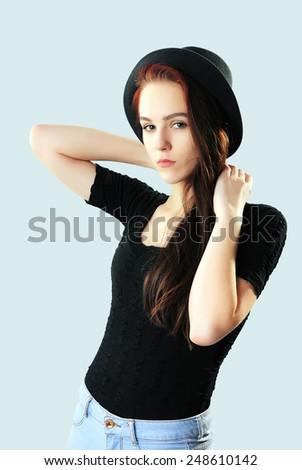 Girl in hat, jeans and black t-shirt - stock photo