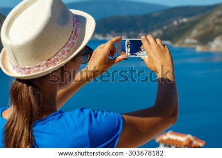 Girl in hat making photos of the smartphone Perast in Boka Kotor Bay, Montenegro, Balkans - stock photo