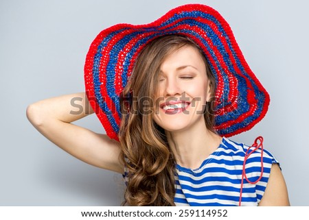 Girl in hat. Marine style. Beautiful woman wearing hat over grey background