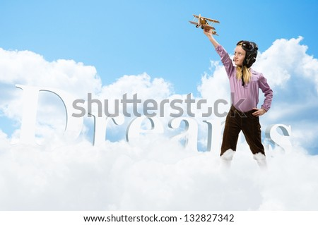 girl in helmet pilot playing with a toy wooden airplane in the clouds, dreaming of becoming a pilot - stock photo