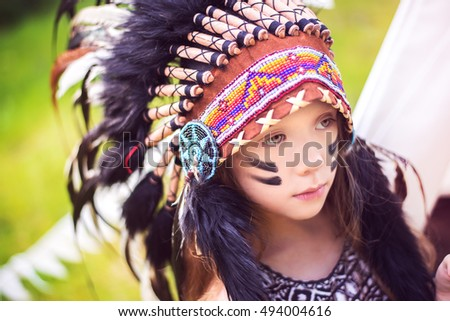 Girl in indian costume with roach wearing on her head, wigwam tent at background