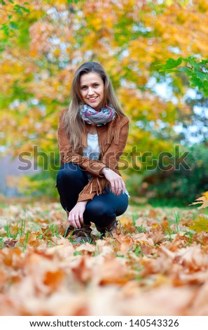 Girl in jacket at autumn park - stock photo