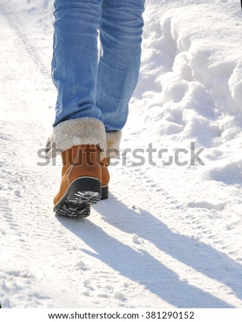 Girl in jeans and yellow boots goes on snow-covered road