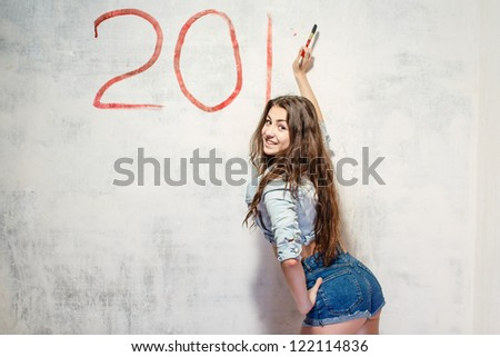 Girl in jeans shorts and jacket draws a Christmas (new year) decoration on old white wall with the red paint.