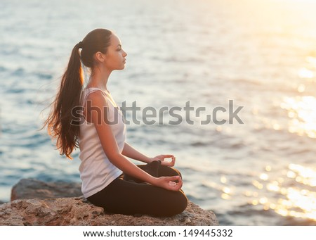 girl in lotus pose at sunset - stock photo