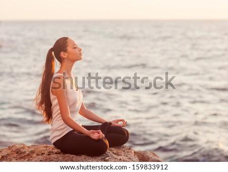 girl in lotus pose at sunset - stock photo