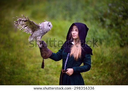 girl in medieval dress is holding an owl on her arm - stock photo