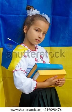 girl  in national ukrainian costume against of Ukrainian flag - stock photo