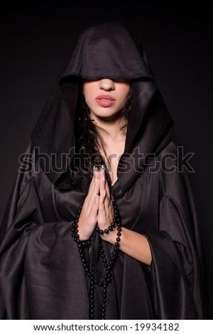 Girl in nun outfit, praying - stock photo