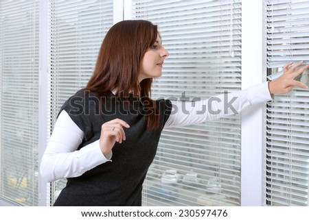 Girl in office peeking through window blinds on the street in anticipation - stock photo