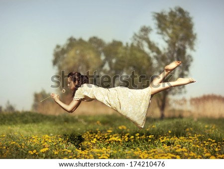 Girl in pajamas night flying over the field and smelling dandelions. - stock photo