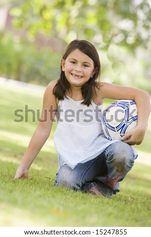 Girl in park holding football looking to  camera - stock photo