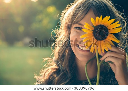 Girl in park smiling and covering face with sunflower - stock photo