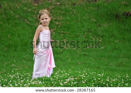 Girl in pink dress on the grass - stock photo