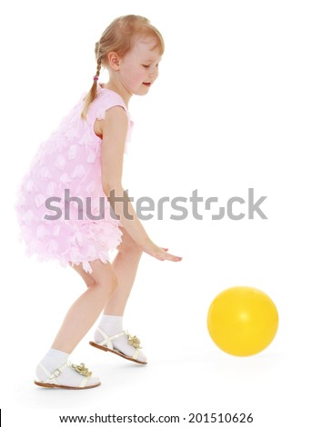 Girl in pink dress playing with a yellow ball.happy childhood,sweet child having fun outdoor,playing isolated on white background, happiness concept,adorable child having fun in studio - stock photo