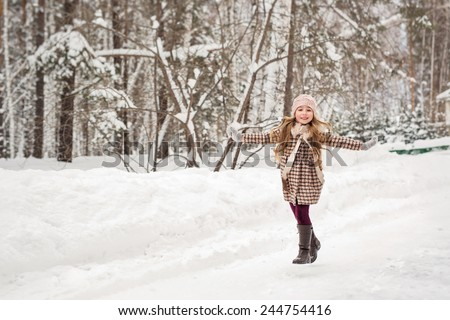 Girl in plaid winter coat happily runs in the winter woods - stock photo