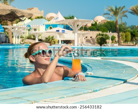 Girl in pool bar at tropical tourist resort vacation destination - stock photo