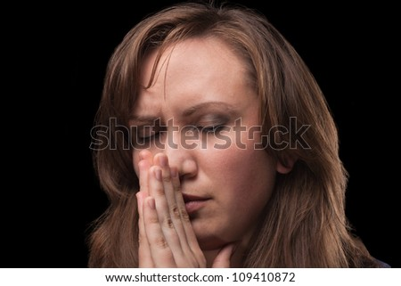 Girl in prayer. Close-up against dark background. His eyes are closed. - stock photo