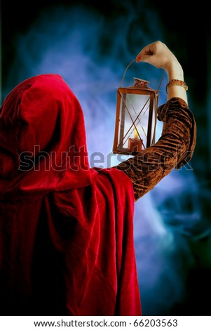 girl in red cloak with a candle-lantern - stock photo