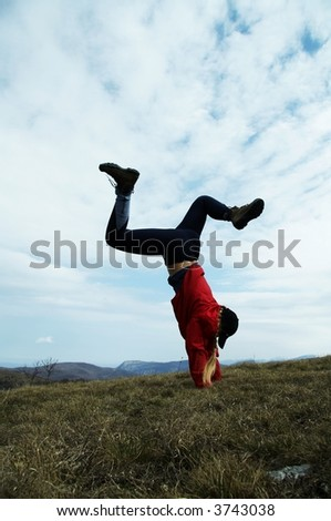 Girl in red clothing is doing cartwheel - stock photo