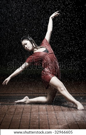 girl in red dancing in the rain - stock photo