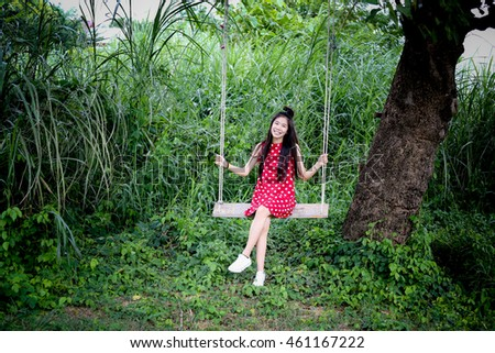 Girl in red dress and she sit on swing