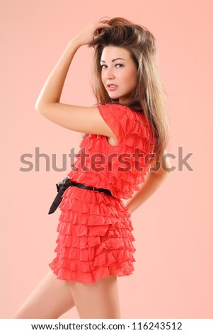 girl in red dress on a pink background - stock photo