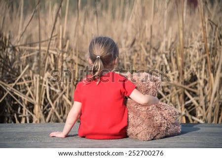 Girl in red dress sitting on a wooden board with teddy bear looking at field of yellow grass - stock photo