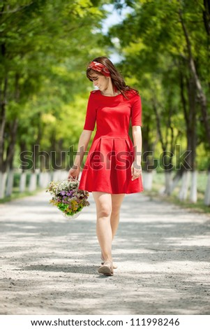 girl in red dress walking in nature with flowers basket