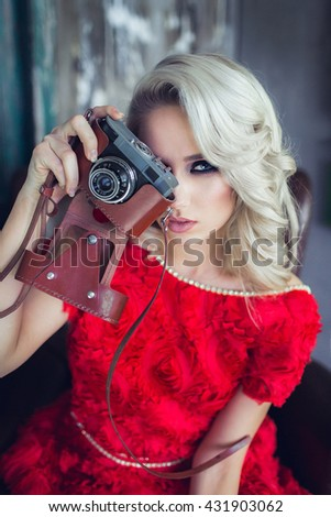 Girl in red dress with vintage retro camera - stock photo