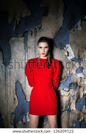 Girl in red over old burned background, studio shot - stock photo