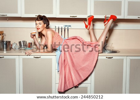 Girl in red shoes climbed on the kitchen table and eat cake. - stock photo