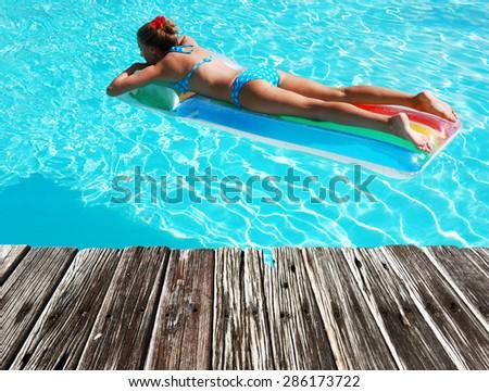 Girl in resort swimming pool - stock photo