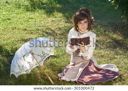 Girl in retro style dress thinks about the novel that she reads outdoors                           - stock photo