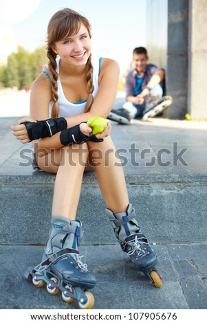 Girl in roller skaters sitting in the foreground and smiling at the cam, her male friend being in the background - stock photo