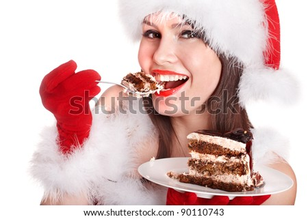 Girl in Santa hat eat cake on plate . Isolated.