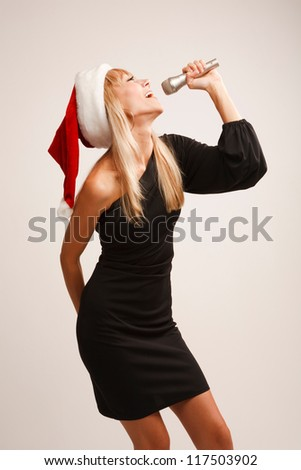 Girl in Santa hat is singing with microphone - stock photo