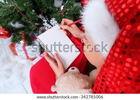 Girl in Santa hat writes letter to Santa near Christmas tree. Young woman writing down wish list in New Year's eve. Top view background with space for your text or design - stock photo