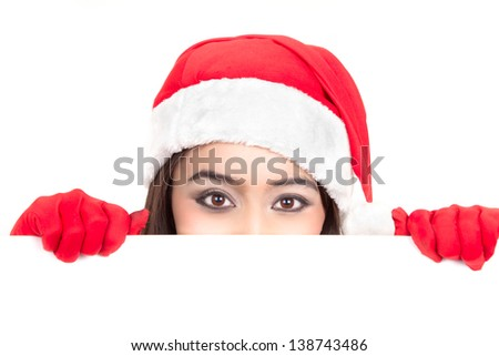Girl in Santa peeking over paper sign board. Cute funny photo closeup of christmas woman with copyspace. Isolated on white background. - stock photo