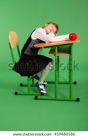 Girl in school uniform sleeping at his desk isolated on green background