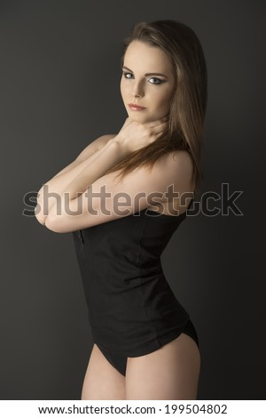 girl in sensual pose with long smooth hair wearing black comfortable underwear, singlet and sexy panties  - stock photo