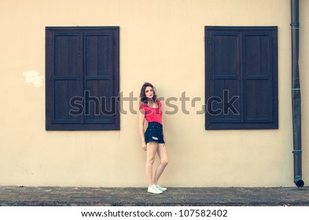 girl in shorts and red t-shirt standing in front of house between two closed windows summer day - stock photo