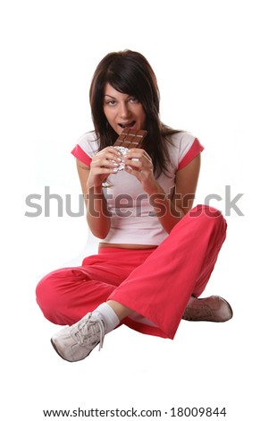 Girl in sports dress eating chocolate - stock photo