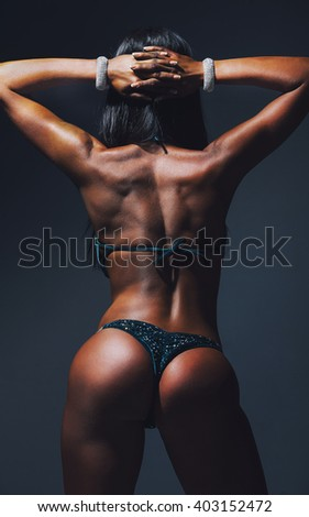 Girl in sports swimsuit. With his back to the camera. Textured leather. Muscles. expensive jewelry on the hands. The combination of health and youth.