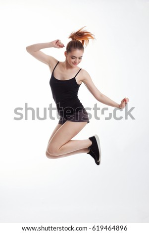 Girl in sports uniforms jumping against a white background